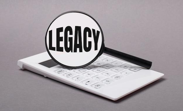 Op grijze achtergrond zwarte rekenmachine en vergrootglas met tekst legacy. bedrijfsconcept