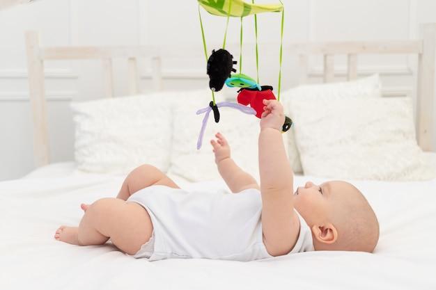 Op het bed in de kinderkamer speelt een kind met een mobiele telefoon