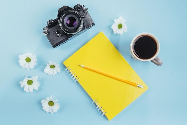 Op het blauwe notitieboekjepotlood, de liniaal en de witte bloemen