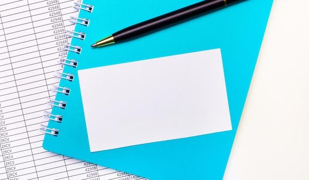 Op het bureau liggen rapporten, een lichtblauw notitieblok, een zwarte pen en een witte blanco kaart met ruimte om tekst in te voegen. stijlvolle werkplek. bedrijfsconcept