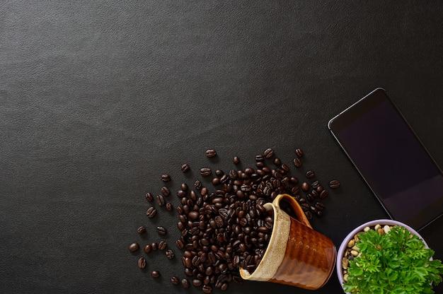 Op het bureau staan koffiebonen en smartphones.