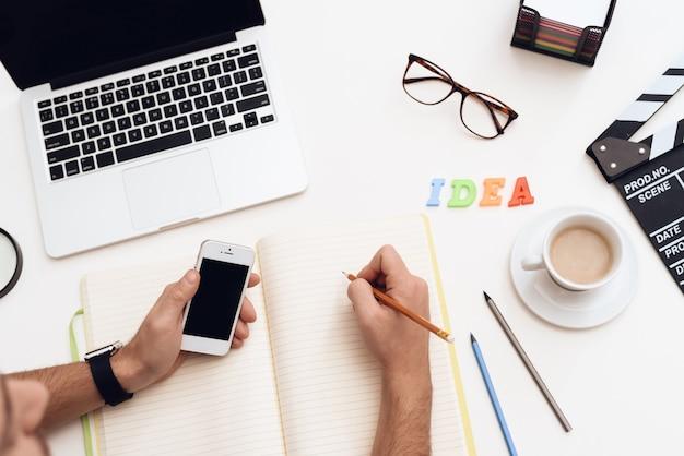 Op het bureau staat een laptop, een kop koffie, een mobiele telefoon.