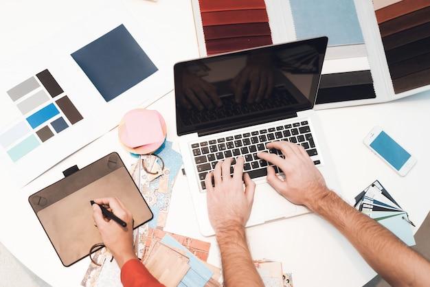 Op het bureau staat een laptop, waarop de man de tekst afdrukt.