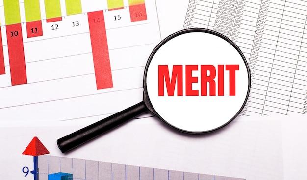 Op het bureaublad grafieken, rapporten, een vergrootglas met de inscriptie merit. bedrijfsconcept.