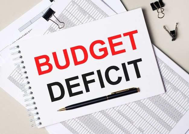 Op het bureaublad staan documenten, pen, zwarte paperclips en een notitieboekje met de tekst budget deficit. bedrijfsconcept