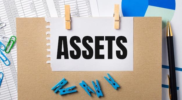 Op het bureaublad staan rapporten, blauwe wasknijpers en kaarten, een pen, een notitieboekje en een vel papier met de tekst assets. bedrijfsconcept