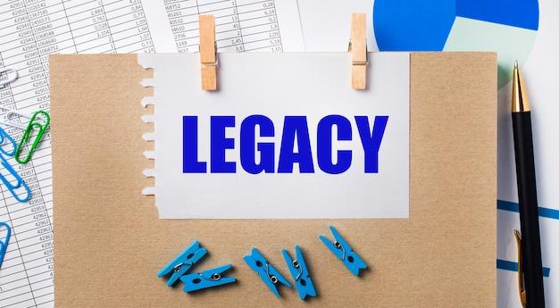 Op het bureaublad staan rapporten, blauwe wasknijpers en kaarten, een pen, een notitieboekje en een vel papier met de tekst legacy. bedrijfsconcept