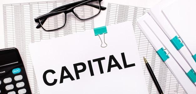 Op het bureaublad staan rapporten, documenten, een bril, een rekenmachine, een pen en papier met de tekst capital. bedrijfsconcept