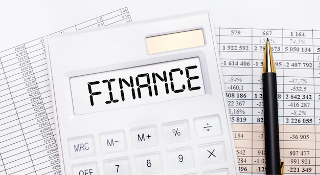 Op het bureaublad staan rapporten, een witte rekenmachine met de tekst finance op het scorebord en een pen. bedrijfsconcept.
