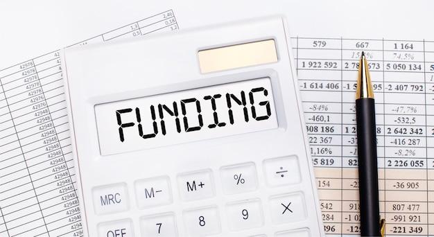 Op het bureaublad staan rapporten, een witte rekenmachine met de tekst funding op het scorebord en een pen. bedrijfsconcept.