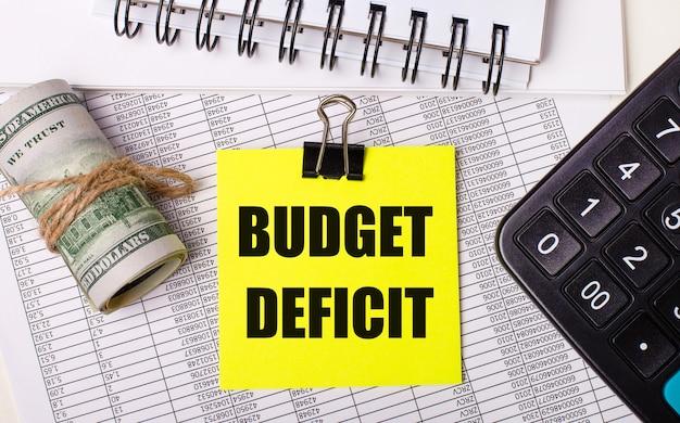 Op het bureaublad staan rapporten, notitieblokken, een rekenmachine, een contant geld en een gele sticker met de tekst budget deficit. bedrijfsconcept