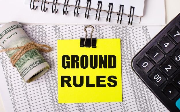 Op het bureaublad staan rapporten, notitieblokken, een rekenmachine, een contant geld en een gele sticker met de tekst ground rules. bedrijfsconcept