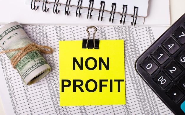 Op het bureaublad staan rapporten, notitieblokken, een rekenmachine, een contant geld en een gele sticker met de tekst non profit. bedrijfsconcept