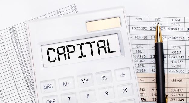 Op het bureaublad staan verslagen, een witte rekenmachine met de tekst capital op het scorebord en een pen. bedrijfsconcept.