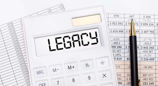Op het bureaublad staan verslagen, een witte rekenmachine met de tekst legacy op het scorebord en een pen. bedrijfsconcept.
