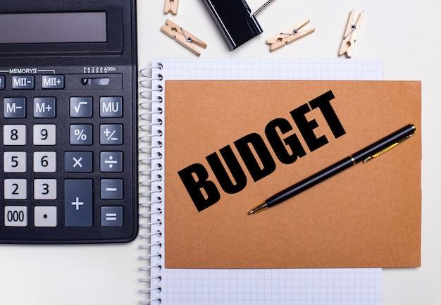 Op het bureaublad staat een rekenmachine, een pen en wasknijpers bij een notitieboekje met de tekst funding. bedrijfsconcept. sjabloon. uitzicht van boven