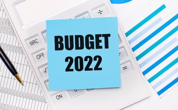 Op het bureaublad staat een witte rekenmachine met een blauwe sticker met de tekst budget 2022, een pen en blauwe rapporten. bedrijfsconcept