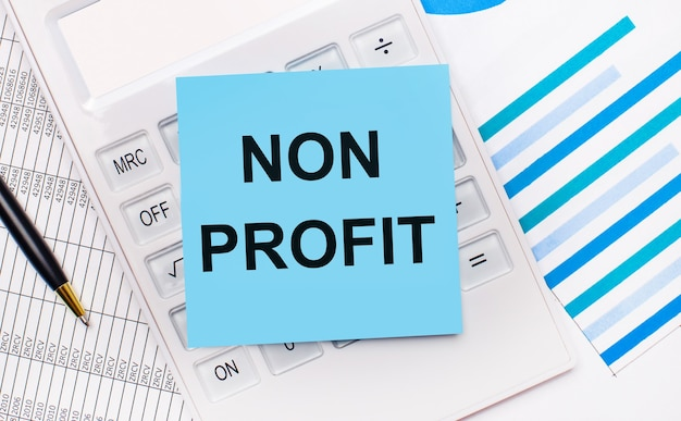 Op het bureaublad staat een witte rekenmachine met een blauwe sticker met de tekst non profit, een pen en blauwe rapporten. bedrijfsconcept