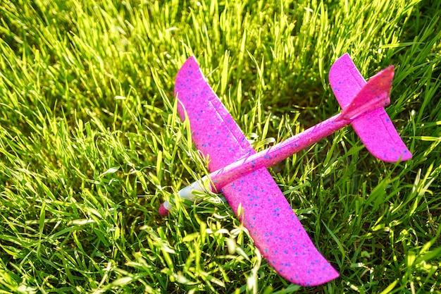 Op het gras ligt een roze plastic kindervliegtuig