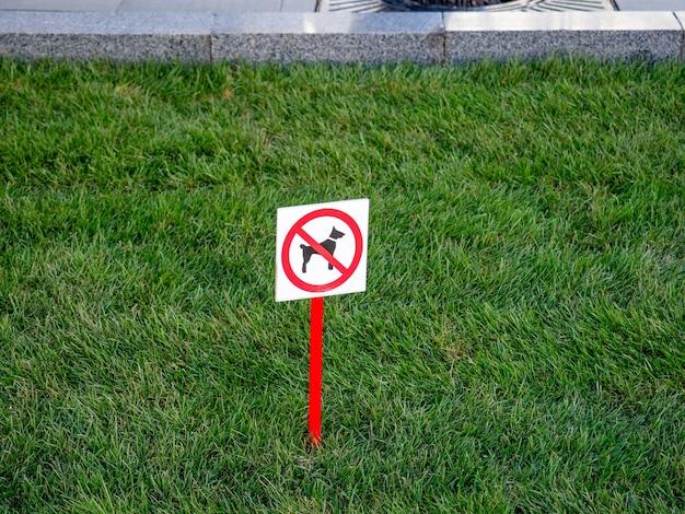 Op het groene grasveld staat een bord met het verbod op het uitlaten van de hond.