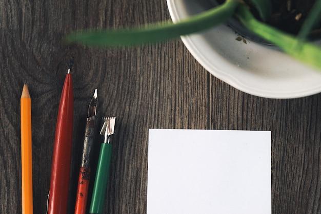 Op het houten oppervlak staan veelkleurige pennen, een groene plant in een pot en wit papier