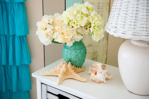 Op het nachtkastje staat een witte lamp en een vaas met bloemen.
