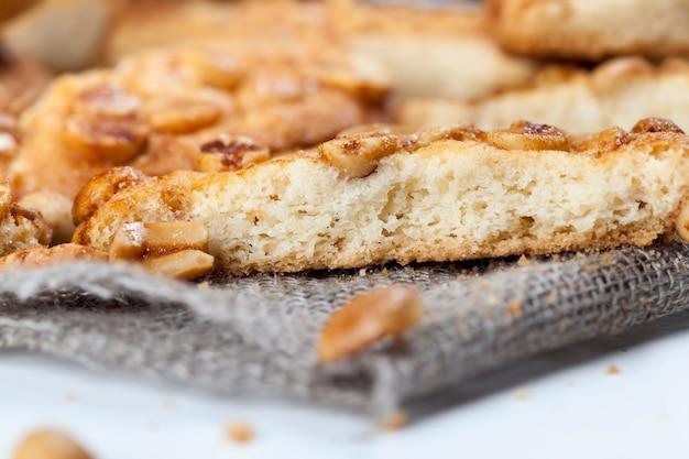 Op het oppervlak van een ronde koekjeskaramel met pinda's, verse knapperige koekjes gemaakt van tarwebloem en geroosterde pinda's, heerlijke koekjes van verschillende ingrediënten