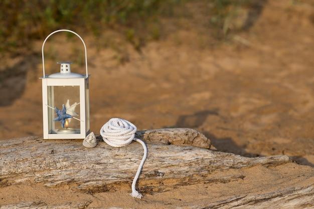 Op het oude houtblok in een lantaarn in nautische stijl, een schaal en een nautisch touw