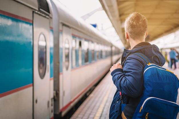 Op het perron bij het treinstation staat een man met een rugzak