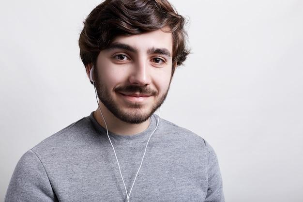 Op het ritme van muziek. een close-up van stijlvolle hipster met baard grote bruine ogen en modern kapsel in oortelefoons met een aangename glimlach