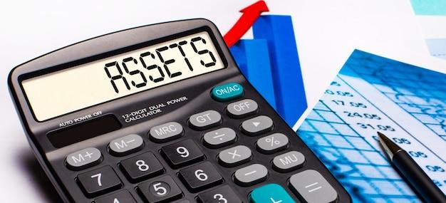 Op het scherm van de rekenmachine staat het opschrift assets. in de buurt zijn gekleurde diagrammen en grafieken. bedrijfsconcept