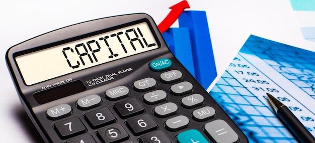Op het scherm van de rekenmachine staat het opschrift capital. in de buurt zijn gekleurde diagrammen en grafieken. bedrijfsconcept
