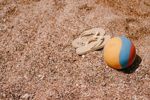 Op het strand liggen veelkleurige bal en beige slippers Premium Foto