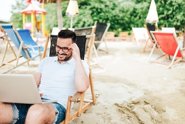 Op het strand met laptop.