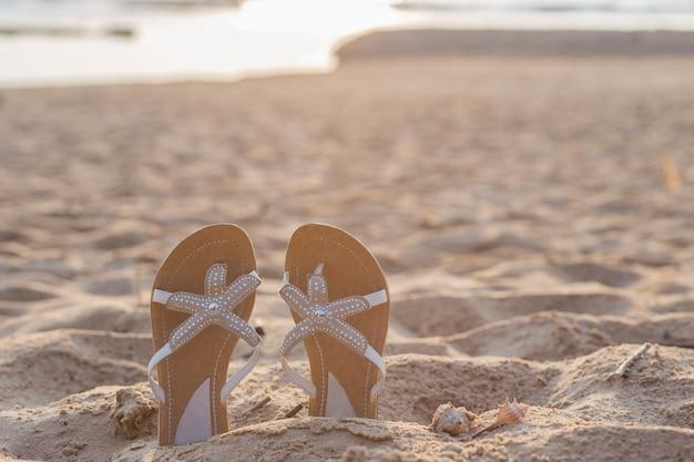 Op het strand steken zandige pantoffels op