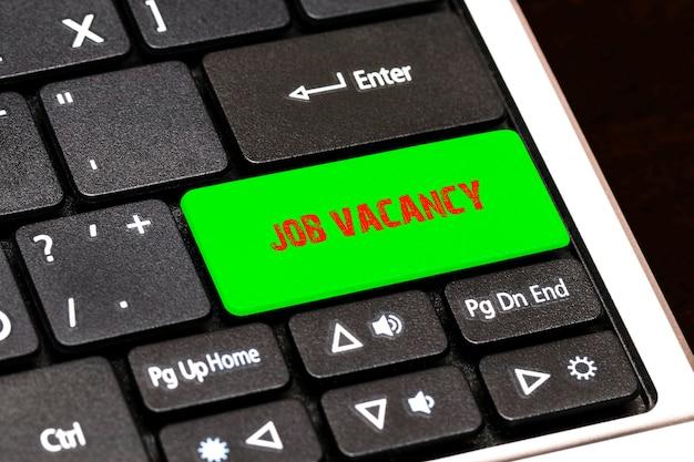 Op het toetsenbord van de laptop schreef de groene knop vacature.
