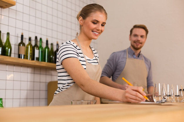Op het werk. vrolijke positieve jonge vrouw glimlachte en kijkt naar haar aantekeningen tijdens het werken in het café