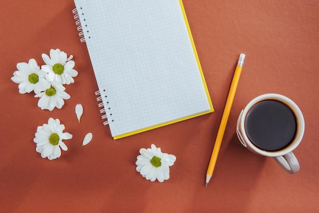 Op houten notitieboekjepotlood, koffie en bloemen.