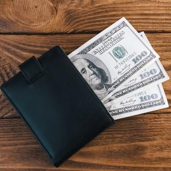 Op houten planken, getextureerde portemonnee met honderd-dollarbiljetten.