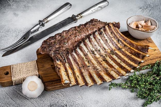 Op houtskool gegrilde franse lamsrack ribs chops op snijplank
