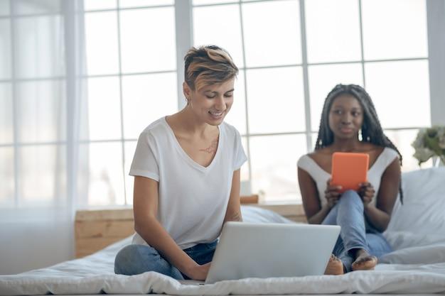 Op internet. twee meisjes zittend op het bed en tijd doorbrengen op internet