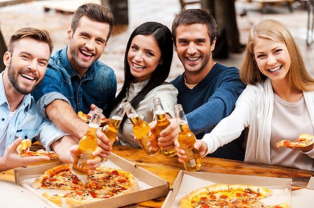 Op jou! groep gelukkige jonge mensen die zich aan elkaar hechten en flessen met bier uitrekken terwijl ze buiten staan