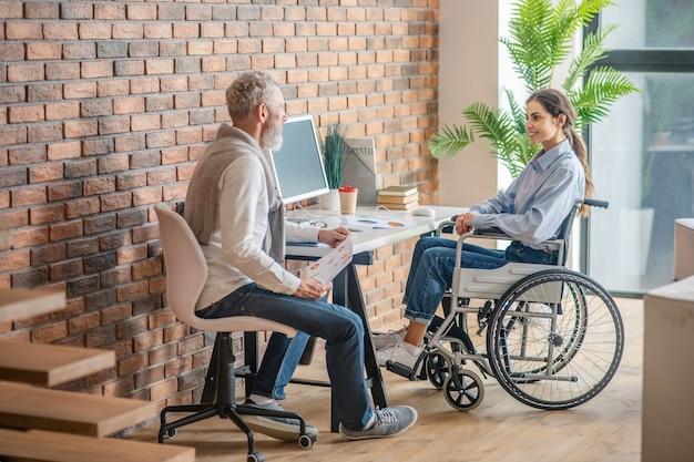 Op kantoor. gehandicapte jonge vrouw zittend aan de tafel op kantoor