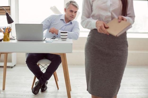 Op kantoor. slimme aardige volwassen man zit aan de tafel en doet alsof hij werkt terwijl hij naar zijn vrouwelijke collega kijkt