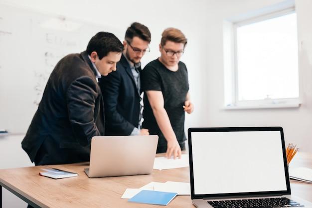 Op kantoor werken drie collega's aan tafel. ze dragen zwarte kleding. aan de voorkant zit een laptopscherm.