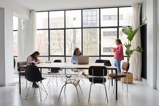 Op kantoor werken drie zakenvrouwen samen zonder maskers op veilige afstand