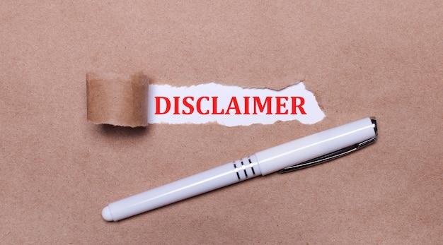 Op kraftpapier, een witte pen en een witte strook papier met de tekst disclaimer.
