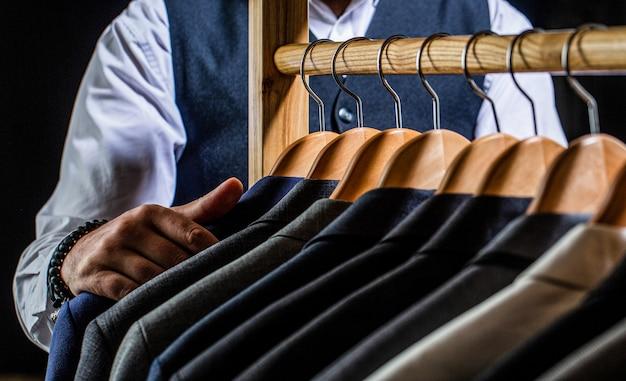 Op maat, maatwerk. stijlvol herenpak. mannelijke pakken die in een rij hangen. herenkleding, boetieks. mannenkostuum, kleermaker in zijn atelier. mode man in klassiek kostuum pak.