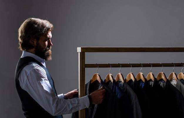 Op maat, maatwerk. stijlvol herenpak. mannelijke pakken die in een rij hangen.