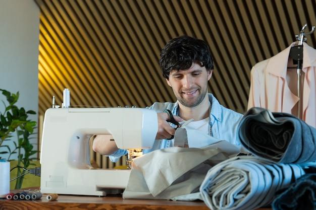 Op maat snijden stof man aan het werk met naaimachine in een textielstudio